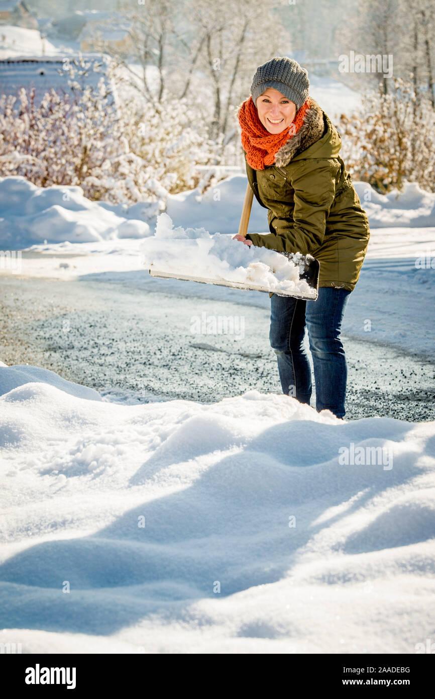 Frau beim Schneeschaufeln - femme n'pelleter la neige Banque D'Images