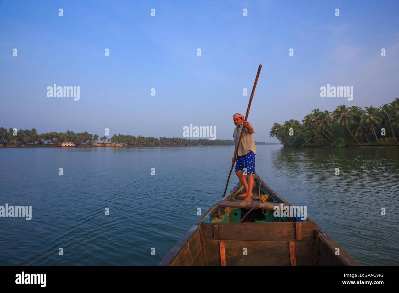 Batelier pousse son bateau avec une rame de bambou dans la rivière serein Suvarna (liste, Karnataka, Inde) Banque D'Images