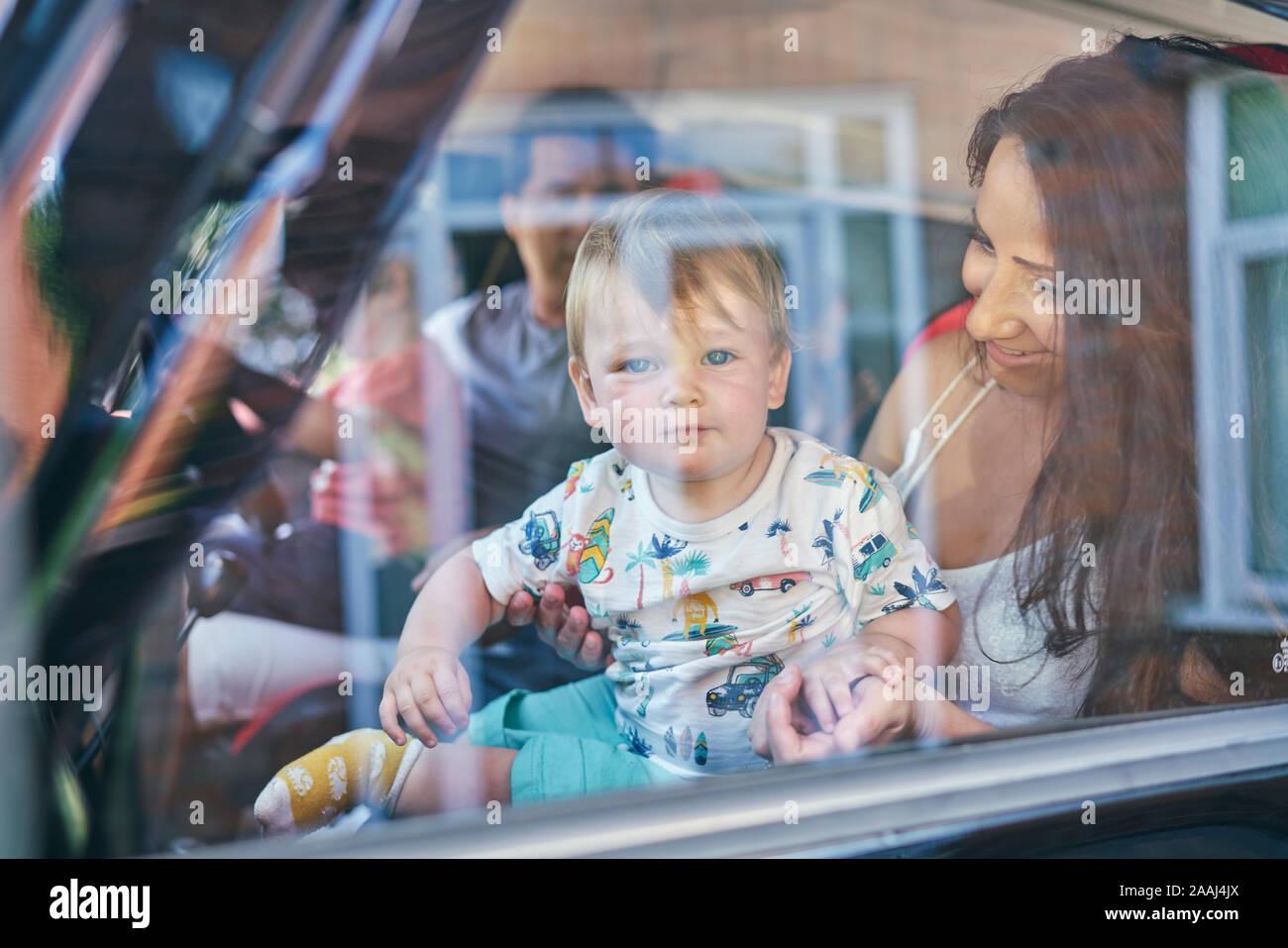 Couple avec enfants assis à l'intérieur voiture Banque D'Images