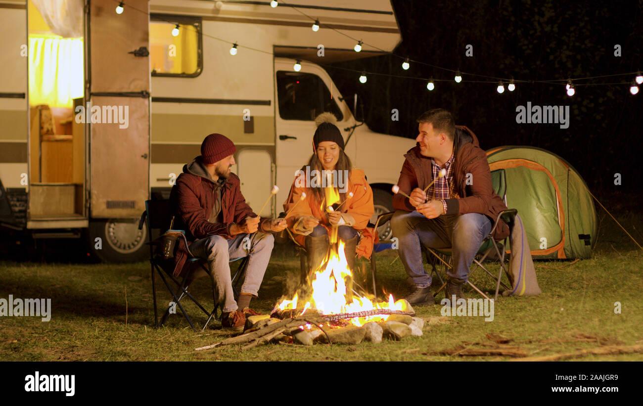 Groupe d'amis heureux autour de brûler le feu camping dans les bois de la torréfaction les guimauves. Retro camping-van. Banque D'Images