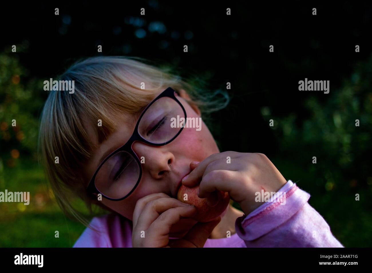 Cute little girl eating apple à la ferme. Vacances d'été à la campagne. Heureux l'enfant sur la nature. Funny kid jouit de l'extérieur au soleil. 24. Organique saine Banque D'Images