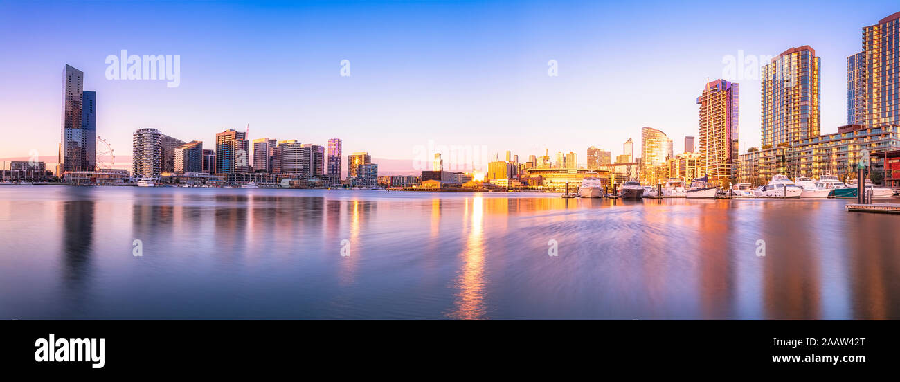Les bâtiments modernes en face de la rivière Yarra au Melbourne Docklands contre le ciel au coucher du soleil, Victoria, Australie Banque D'Images