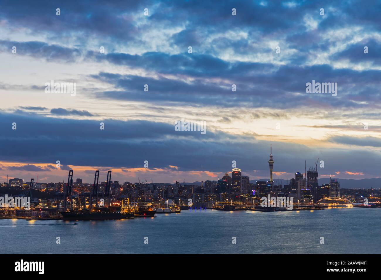 Les bâtiments modernes par mer contre ciel nuageux au crépuscule dans Auckland, Nouvelle-Zélande Banque D'Images