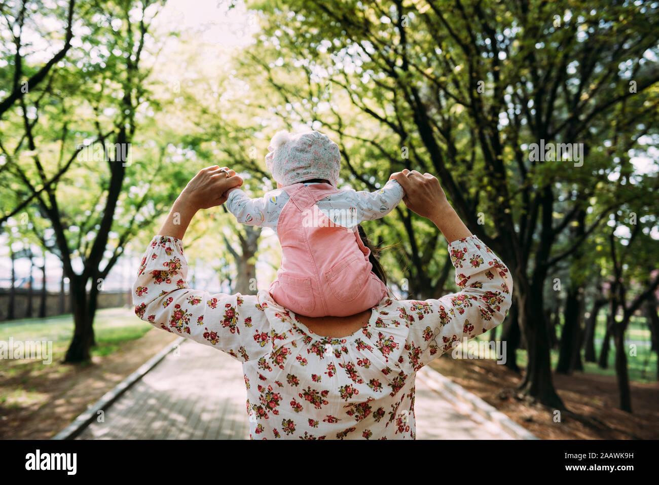 Mère marcher dans un parc avec bébé fille sur ses épaules Banque D'Images