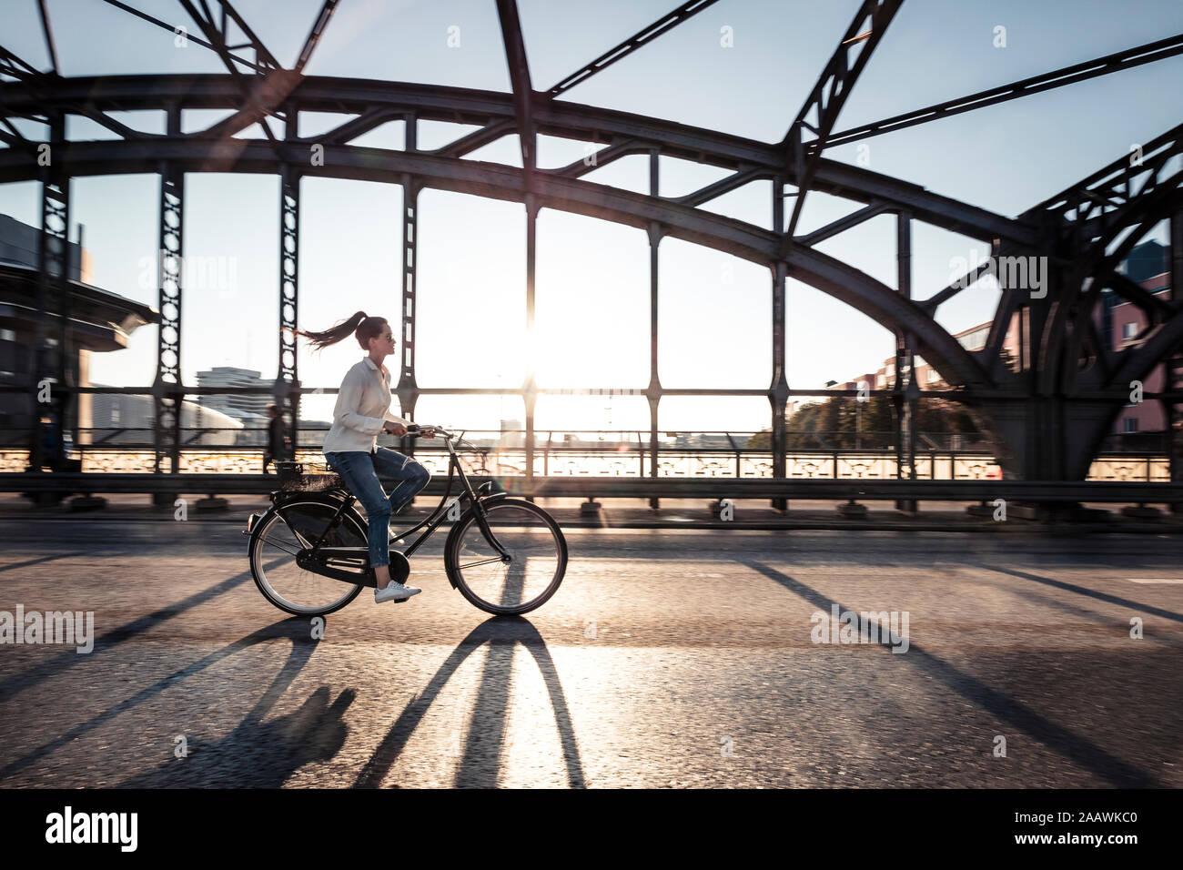 Les jeunes cyclistes sur un pont au coucher du soleil Banque D'Images