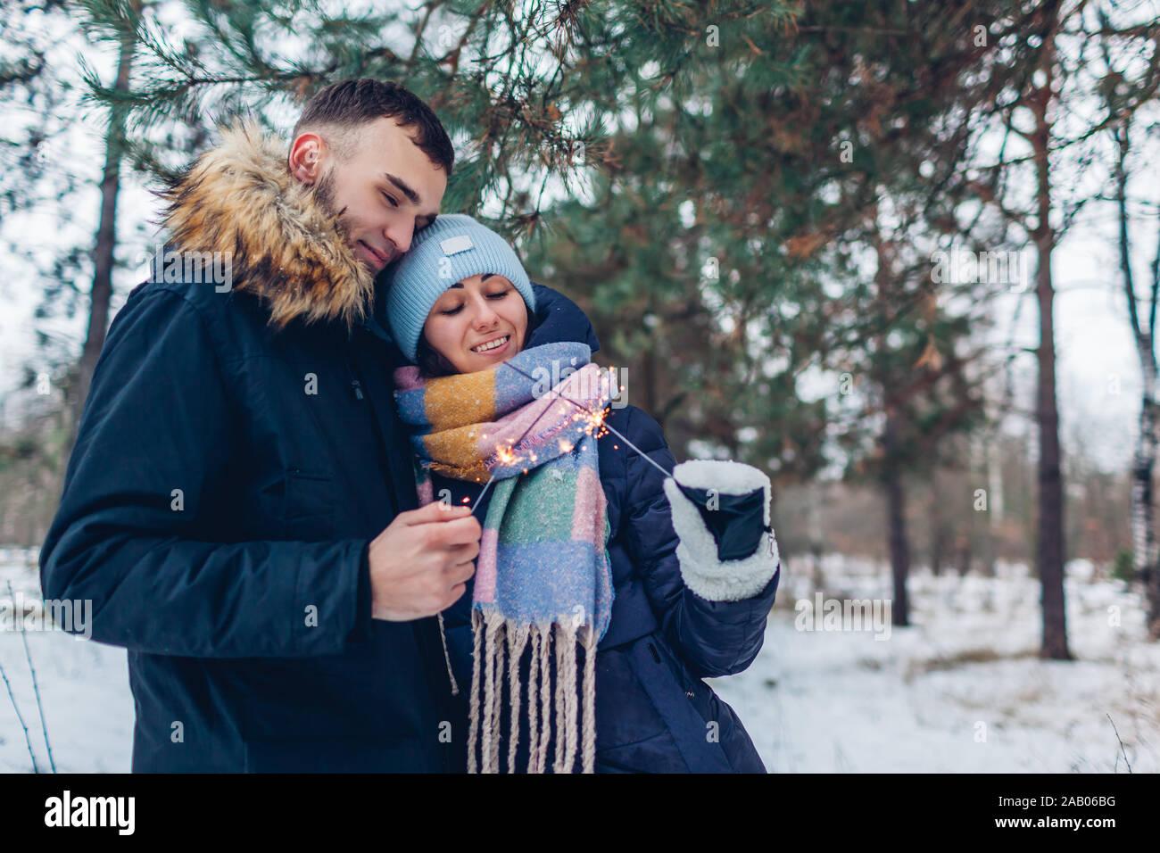 Couple aimant cierges brûlant dans la forêt d'hiver. Noël et Nouvel an concept. Les gens célébrant les jours fériés Banque D'Images