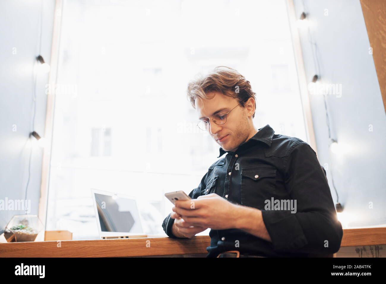 Ambiance jeune professionnel surfer sur Internet sur son ordinateur portable dans un café Banque D'Images