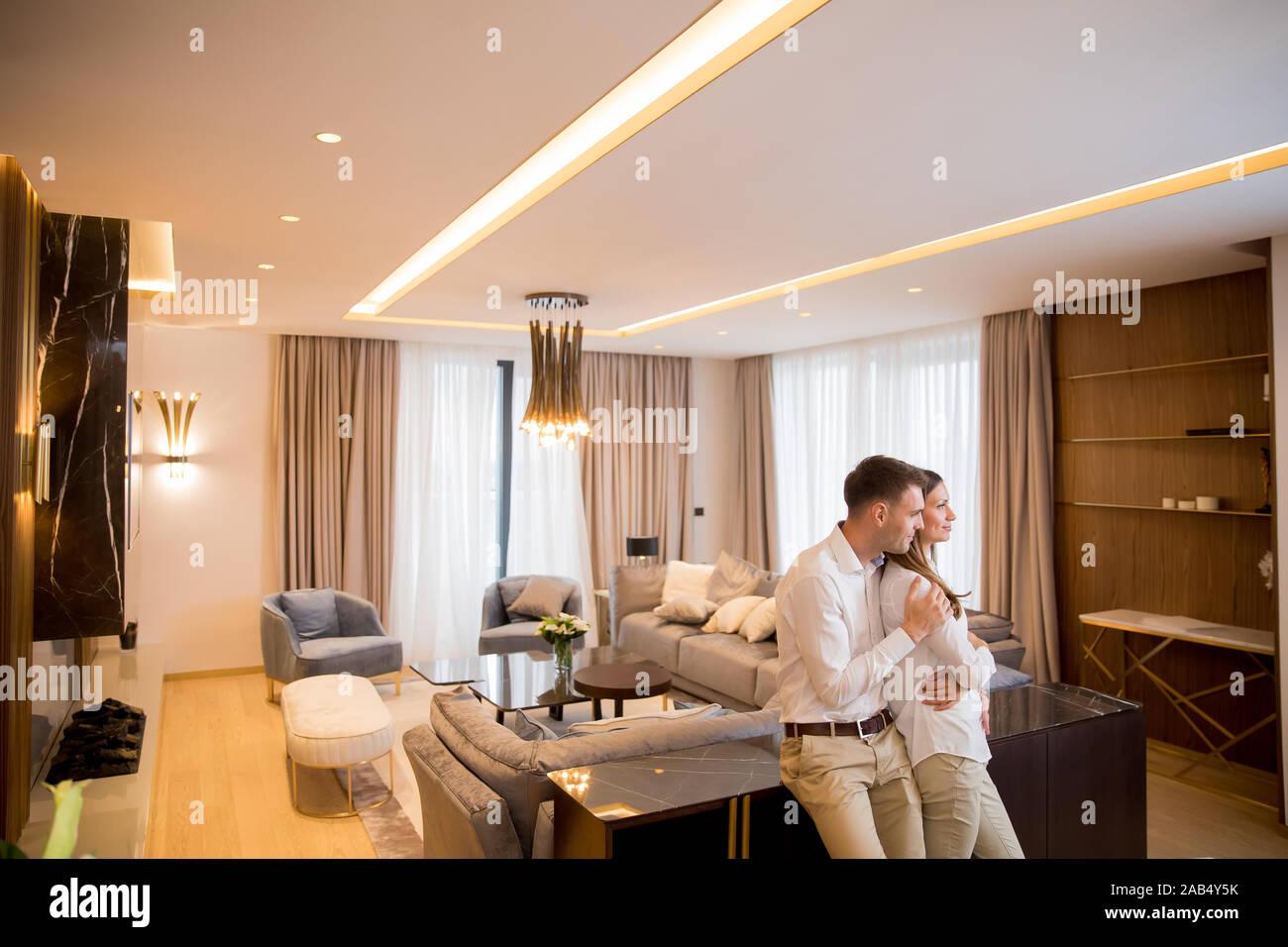 Couple debout dans la salle de séjour d'un appartement contemporain Banque D'Images