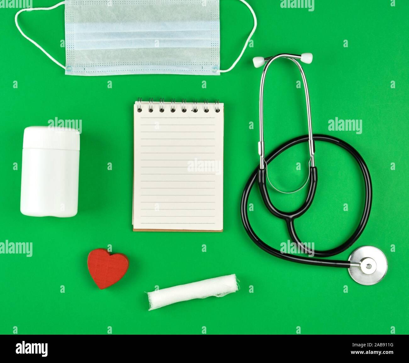 Ordinateur portable ouvert en ligne avec des draps blancs, masque médical, stéthoscope et bandage sur un fond vert. Banque D'Images