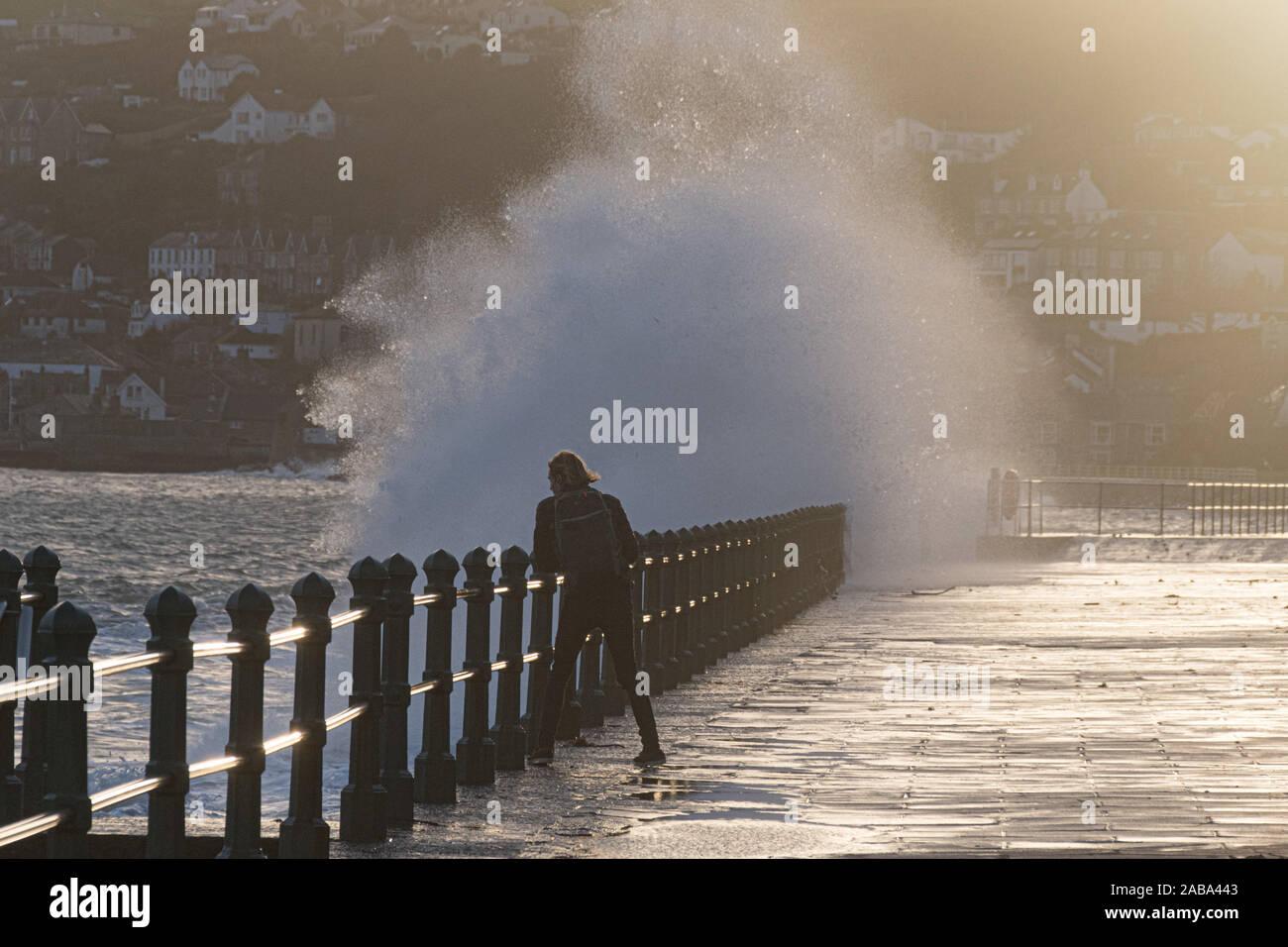 Penzance, Cornwall, UK. 26 novembre 2019. Météo britannique. Un photographe dés avec le danger d'essayer de saisir des images de l'énormes vagues qui se fracassent sur le front de mer à Penzance que storm Sébastien pousse des vagues énormes à l'intérieur des terres. Beaucoup de Cornwall est sur alerte aux crues torrentielles avec pluie prévue pour plus tard. Maycock / AlamyLive Simon crédit News. Banque D'Images
