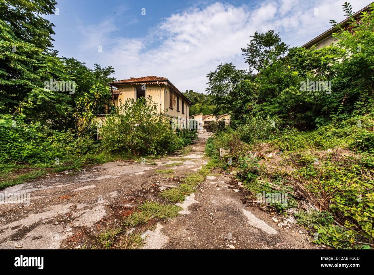 Route cahoteuse qui mène à un grand complexe industriel abandonné, un paysage de l'exploration urbaine aussi connu comme urbex Banque D'Images