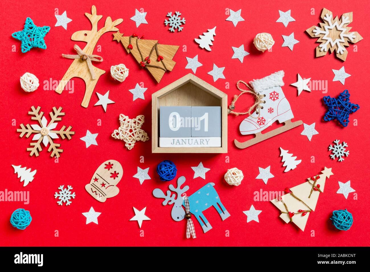 Vue de dessus du calendrier en bois, maison de jouets et des décorations de Noël fond rouge. La première de janvier. Nouveau concept de temps de l'année. Banque D'Images