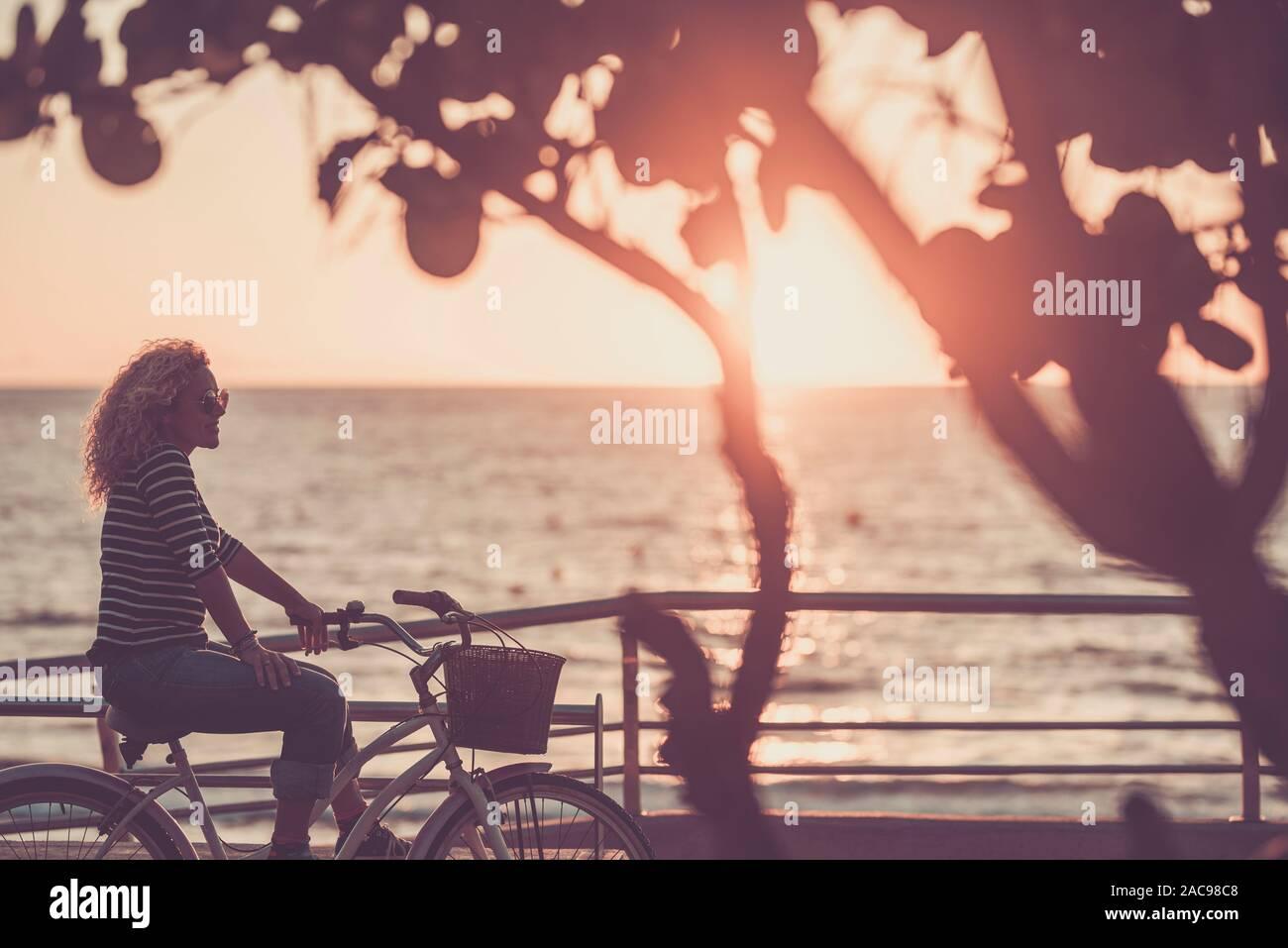Belle femme de race blanche adultes avec des cheveux blonds pour le coucher du soleil avec vue sur la mer de l'océan sur un vélo à la mode vintage - activité de loisirs et de plein air Banque D'Images