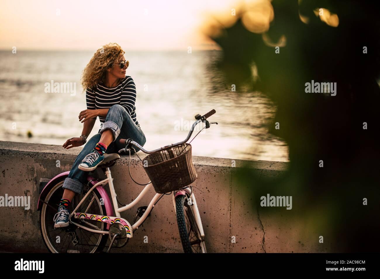 Des profils caucasian woman enjoying extérieure activité de loisirs détente après une balade sur un vélo vintage, assis sur un mur à la recherche à l'ocean -actif sain Banque D'Images