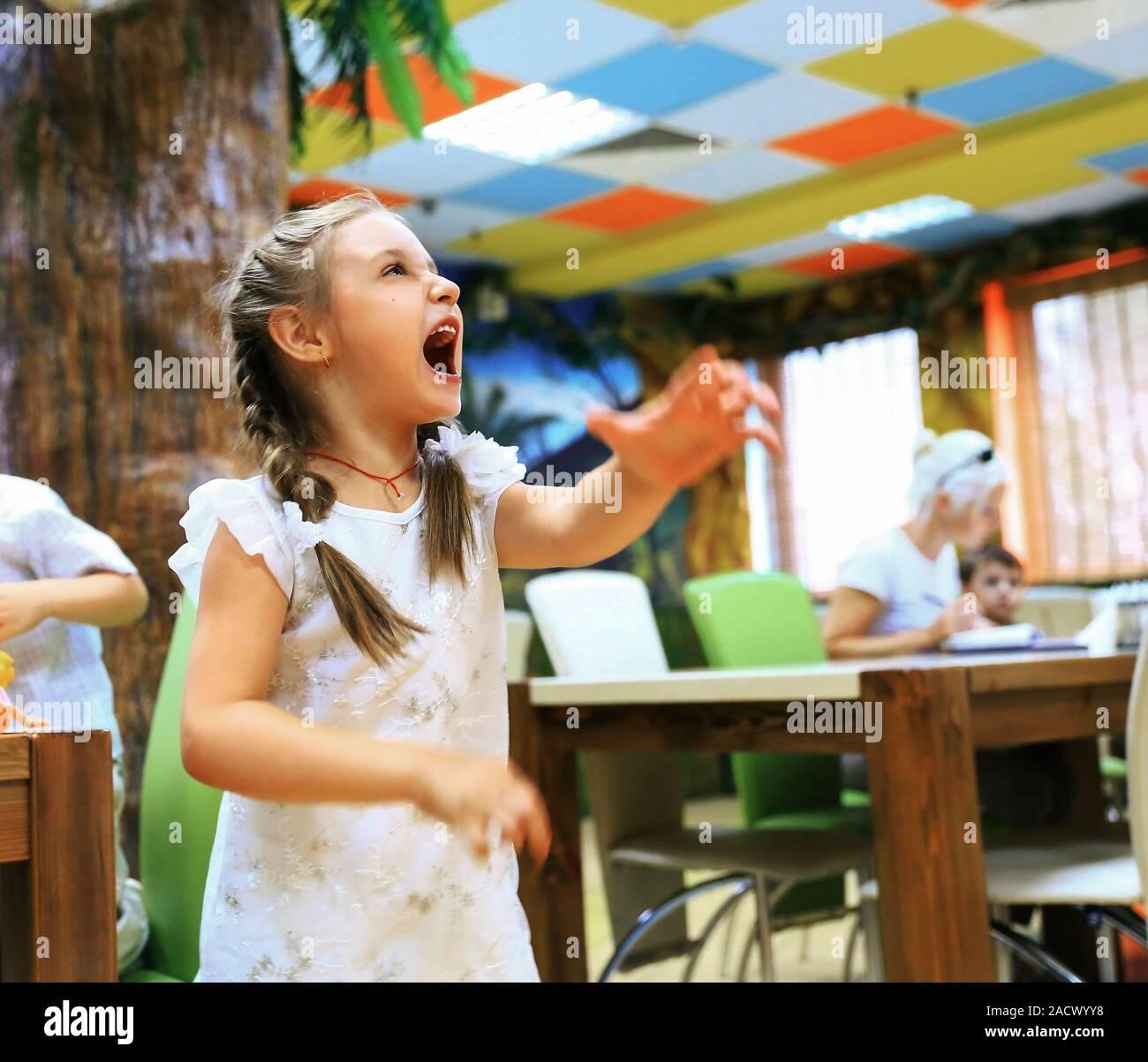Petite fille faisant un drôle de visage.Le concept du jeu. Banque D'Images