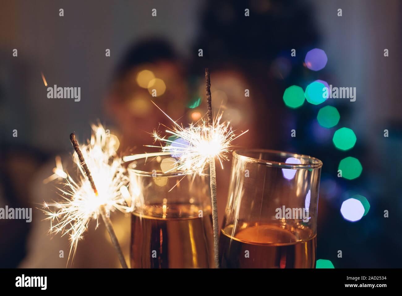 Noël et Nouvel an party concept. Couple amoureux cierges brûlant par Sapin Noël avec champagne. Banque D'Images