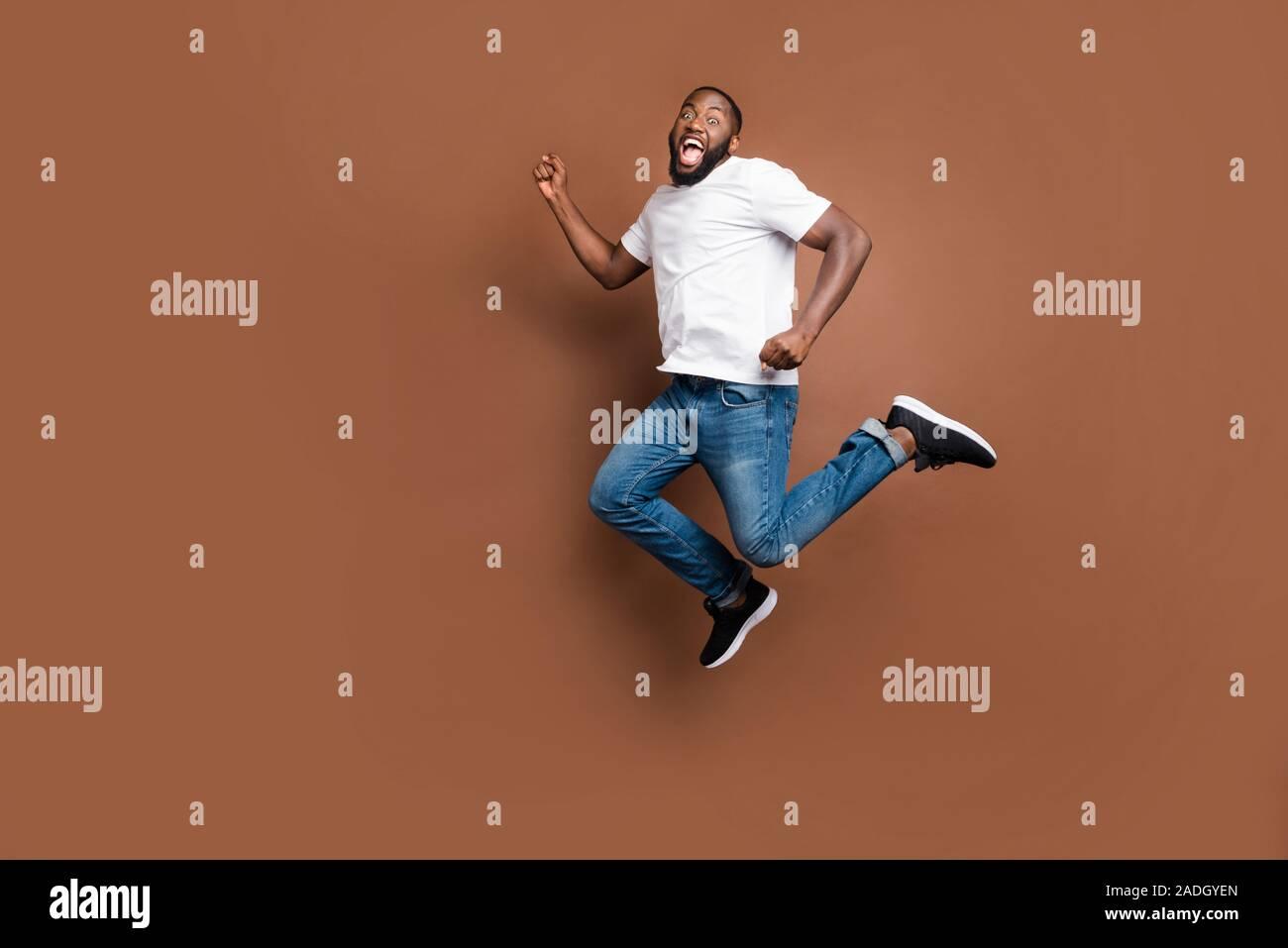 La taille du corps sur toute la longueur de course saut photo urgent crier guy qui aspirent à terminer à la poursuite de ses buts portant des jeans denim blanc T-shirt isolated Banque D'Images