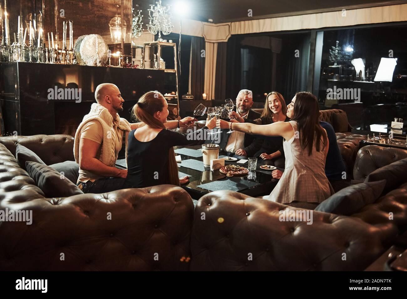 Amis de la famille ont de belles soirée près de la cheminée dans le restaurant moderne de luxe Banque D'Images