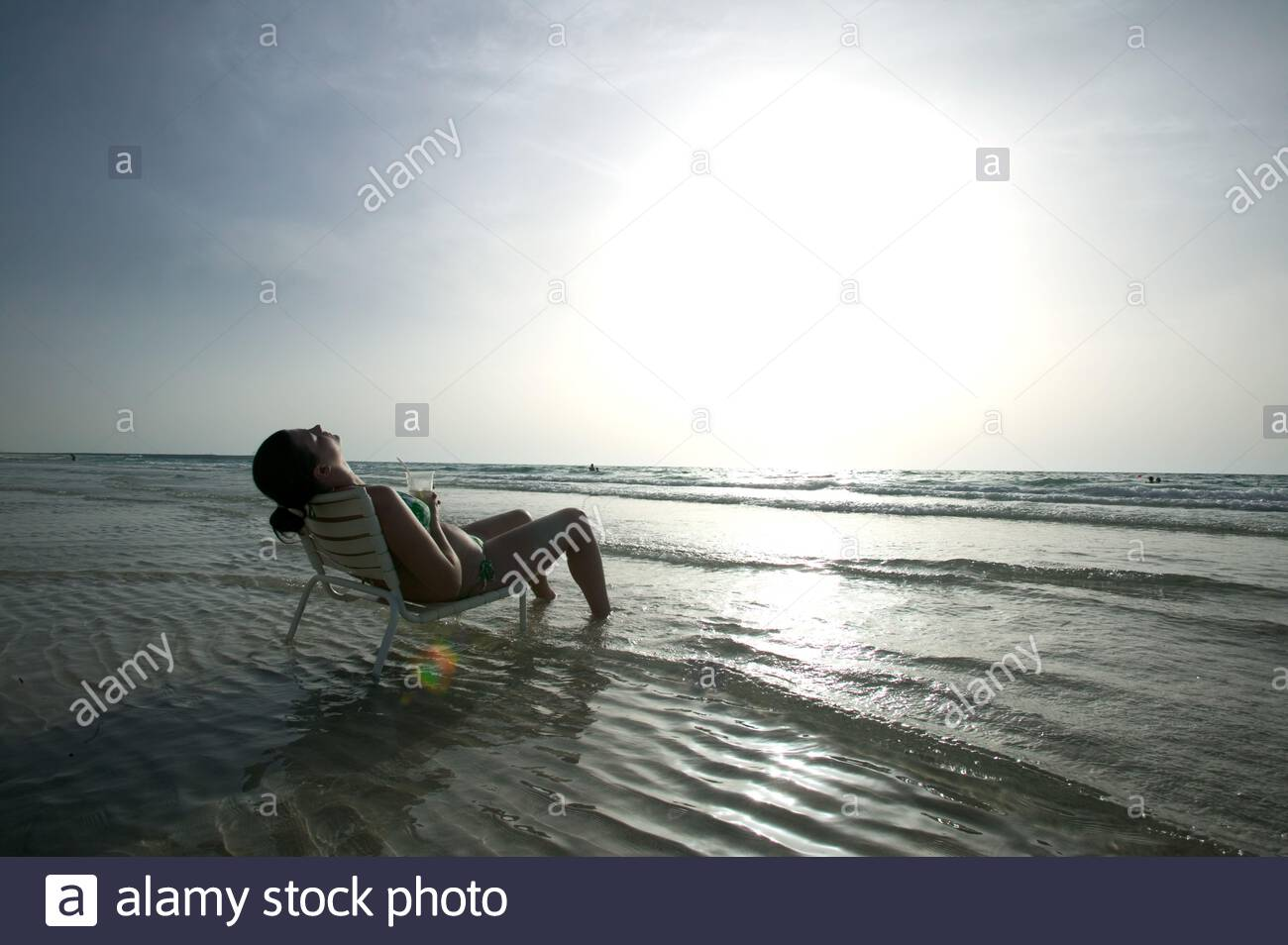 Une personne se détend dans les eaux de la plage privée à Marina de Dubaï, DUBAÏ, ÉMIRATS ARABES UNIS. Banque D'Images