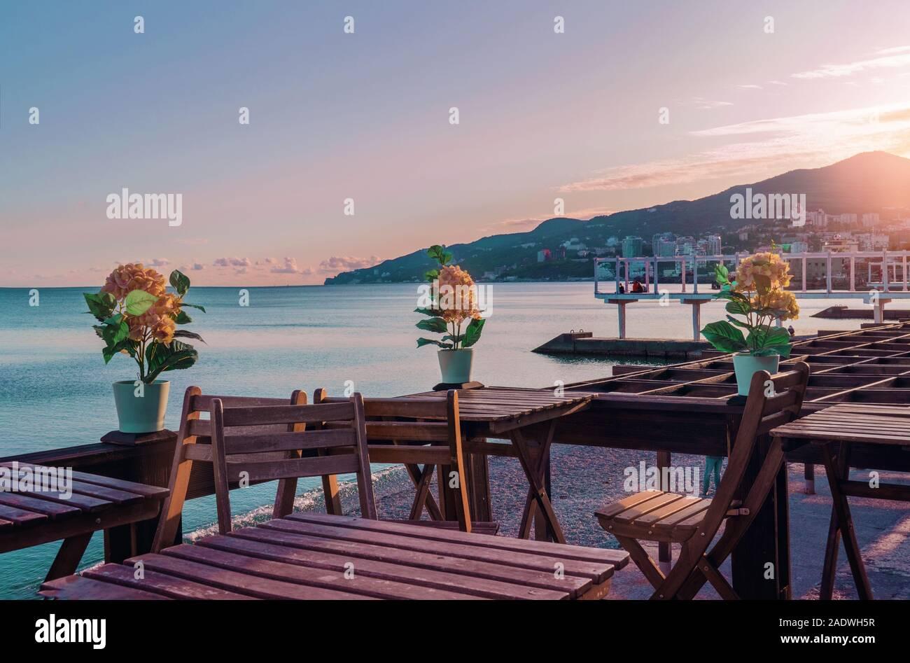 Vue sur la côte. Tables et chaises en bois au bord de l'eau par la mer. Plage Massandra, Yalta, en Crimée. Banque D'Images