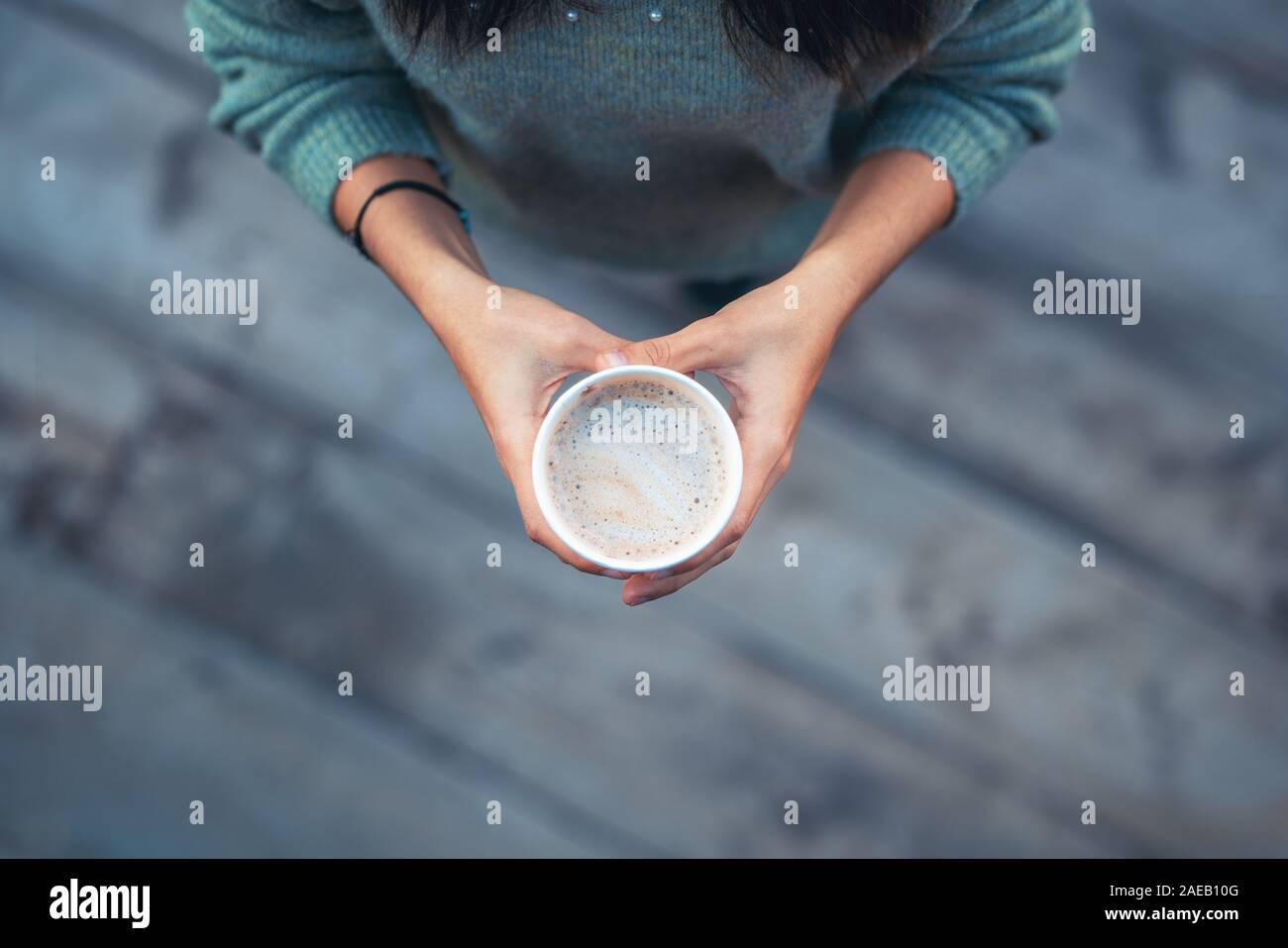 Femme tenant une tasse de papier d'un délicieux café. Banque D'Images