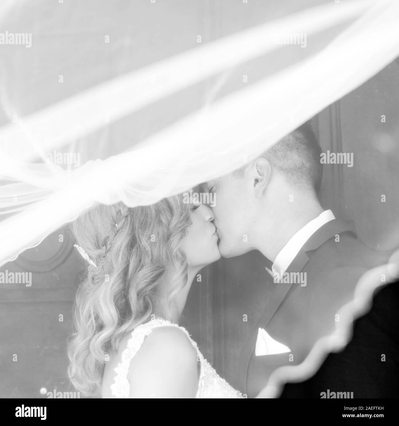 Le baiser. Mariée et le marié embrasse tendrement