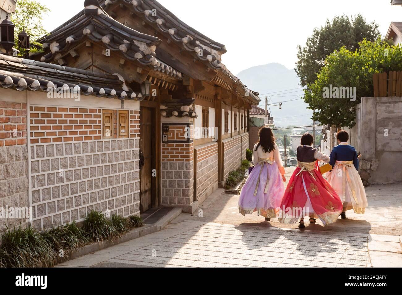 Séoul, Corée du Sud - 21 juin 2017: trois jeunes femmes à porter hanbok traditionnels colorés - marche dans la rue, dans le village de Bukchon Hanok à Séoul. Banque D'Images