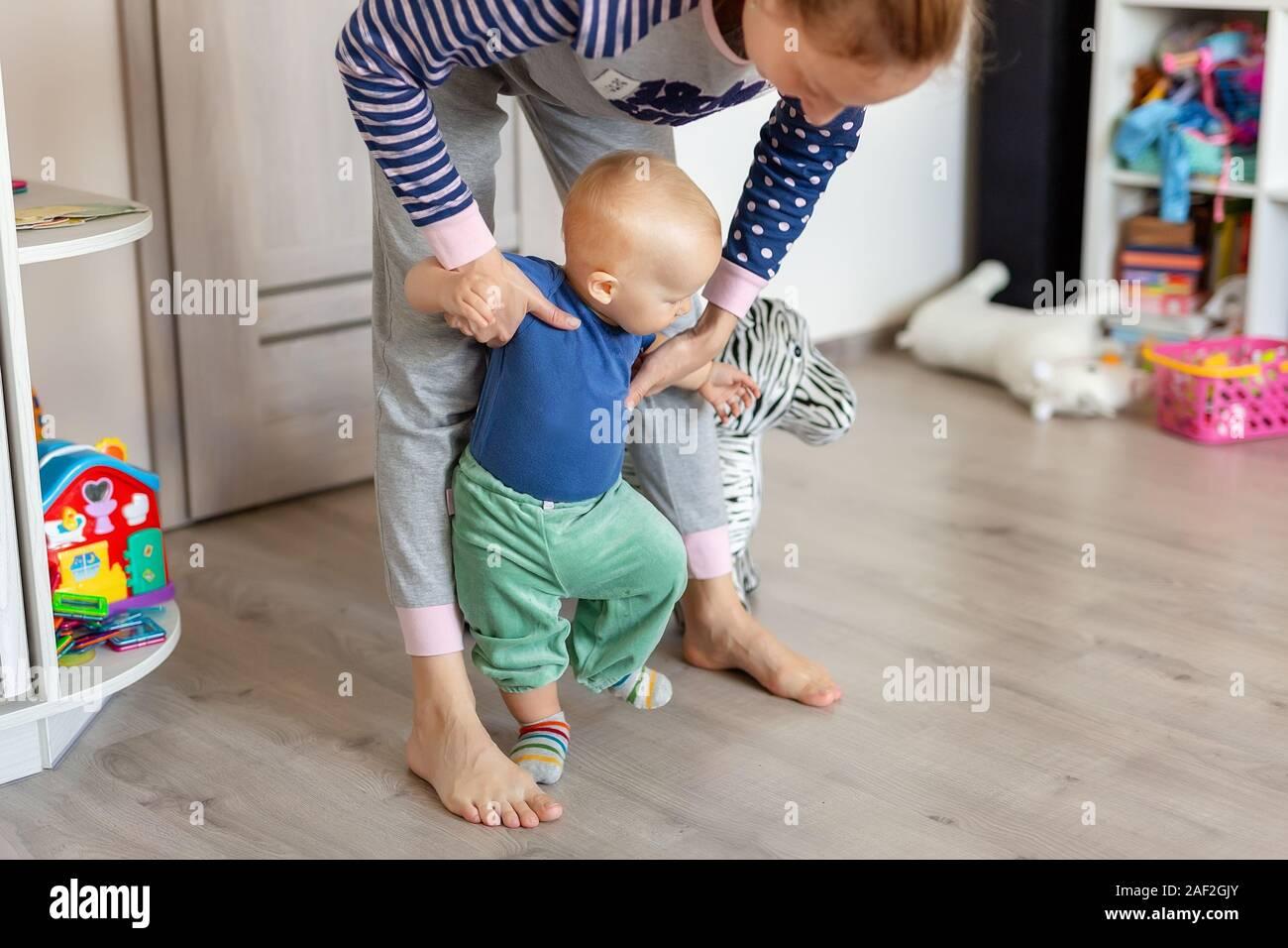 Jolie petite blonde adorable bébé garçon faire les premières étapes avec le soutien aux mères dans les jeux à la maison. Happy funny enfant qui apprend à marcher avec l'aide de MOM Banque D'Images