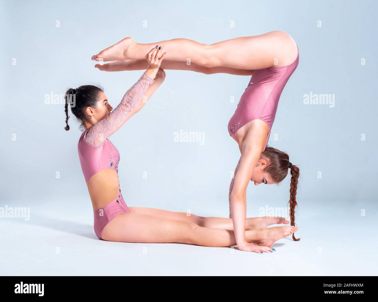 Deux gymnastes filles souples en rose justaucorps font des exercices avec l'appui et posant isolé sur fond blanc. Close-up. Banque D'Images