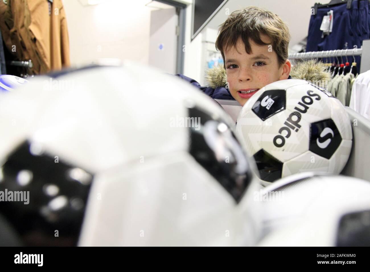 Un monsieur jeune garçon regarde au-dessus d'un rack de Sondico en ballons de sport JD, 2019 Banque D'Images