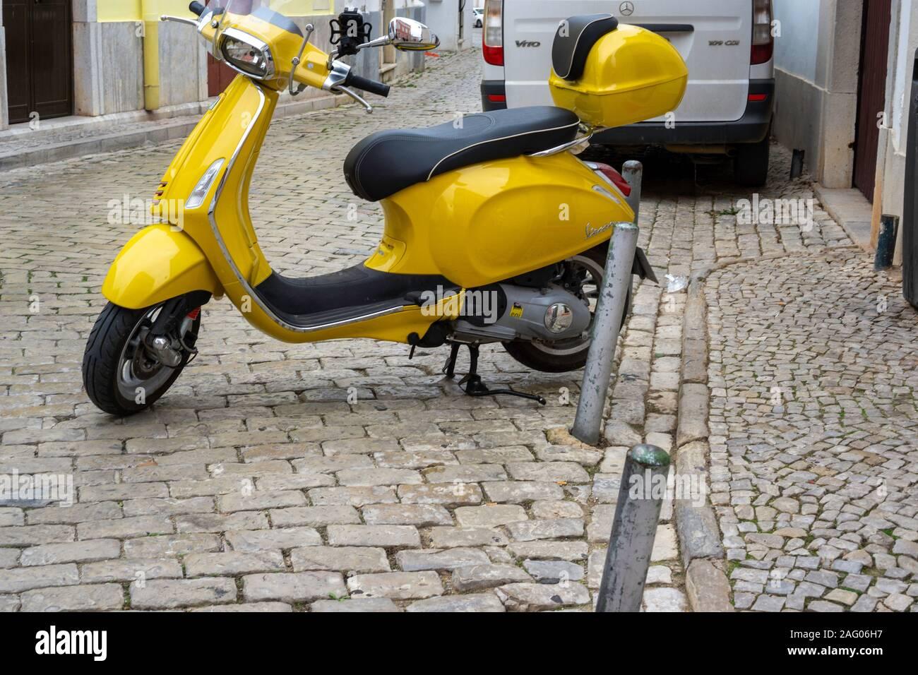 .Un scooter Vespa jaune garée sur une route pavée à Almancil, Portugal Banque D'Images