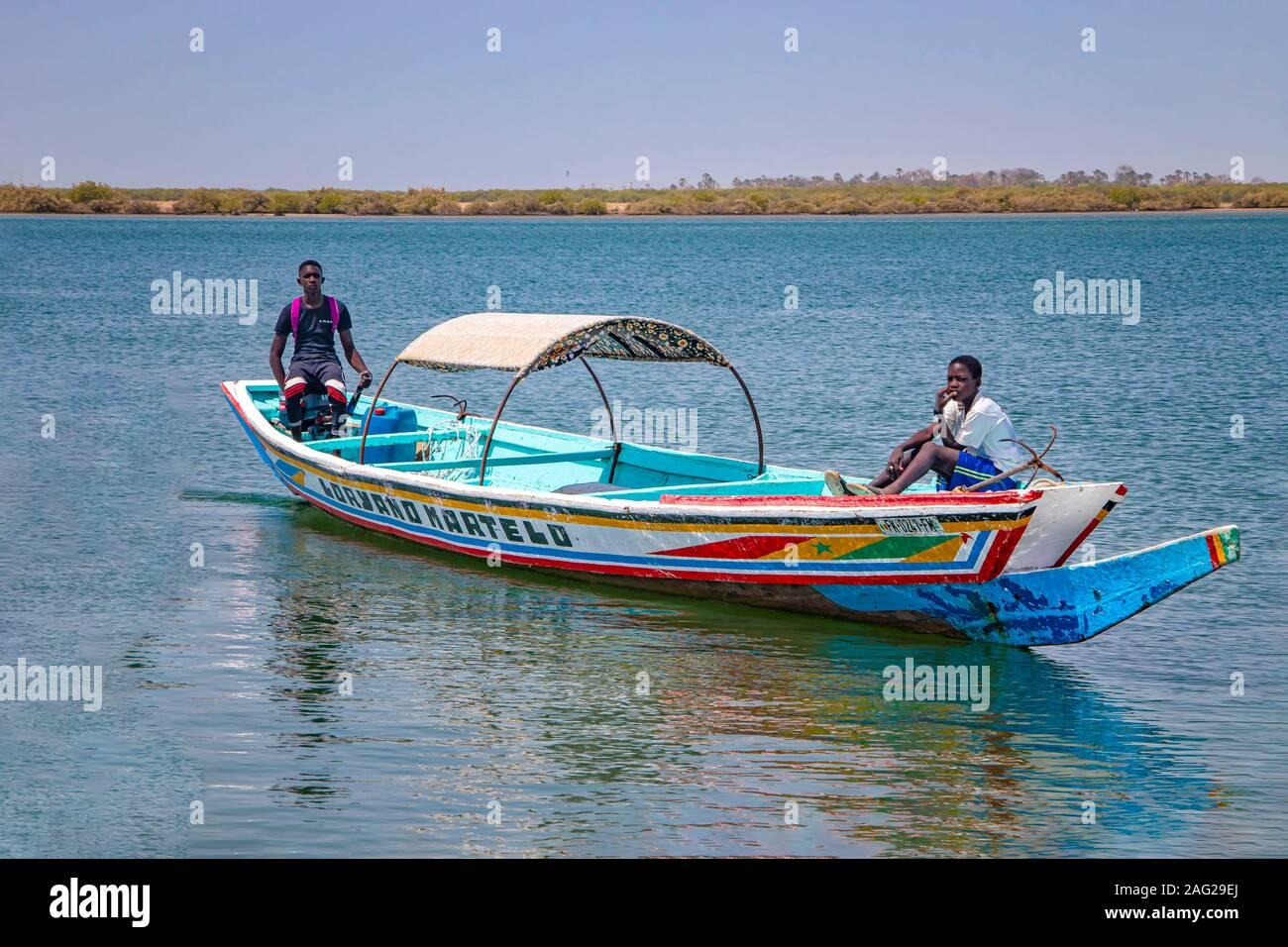 Lagune de Somone, Sénégal- le 26 avril 2019: deux garçons sur un voile coloré en bois typique du canot dans le Sénégal, l'Afrique. Banque D'Images