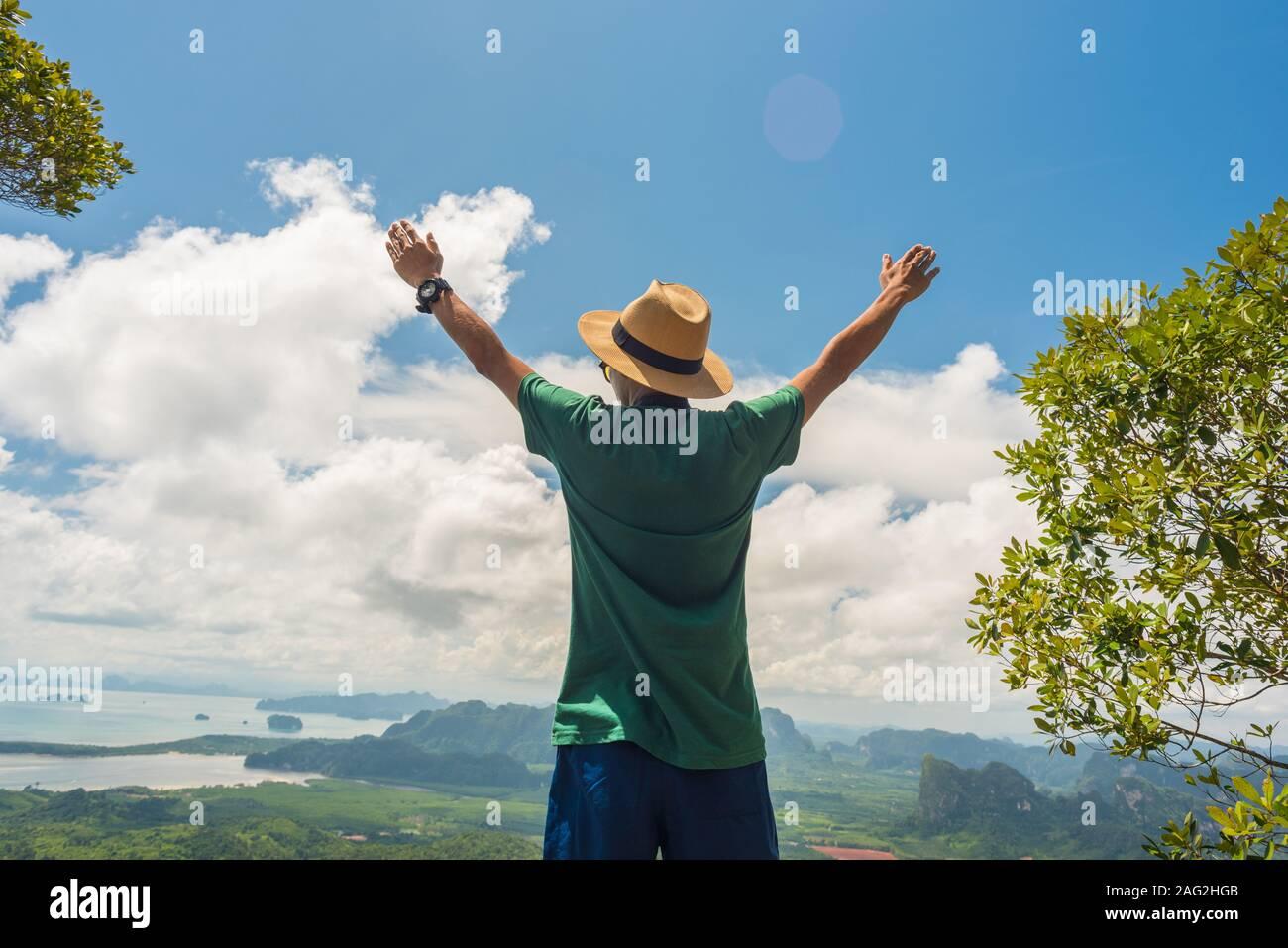 Image Stock: une personne avec les mains levées jusqu'se dresse au sommet de la montagne. Concept de la réussite, les modes de vie, l'harmonie avec la nature et voyager en vacances Banque D'Images