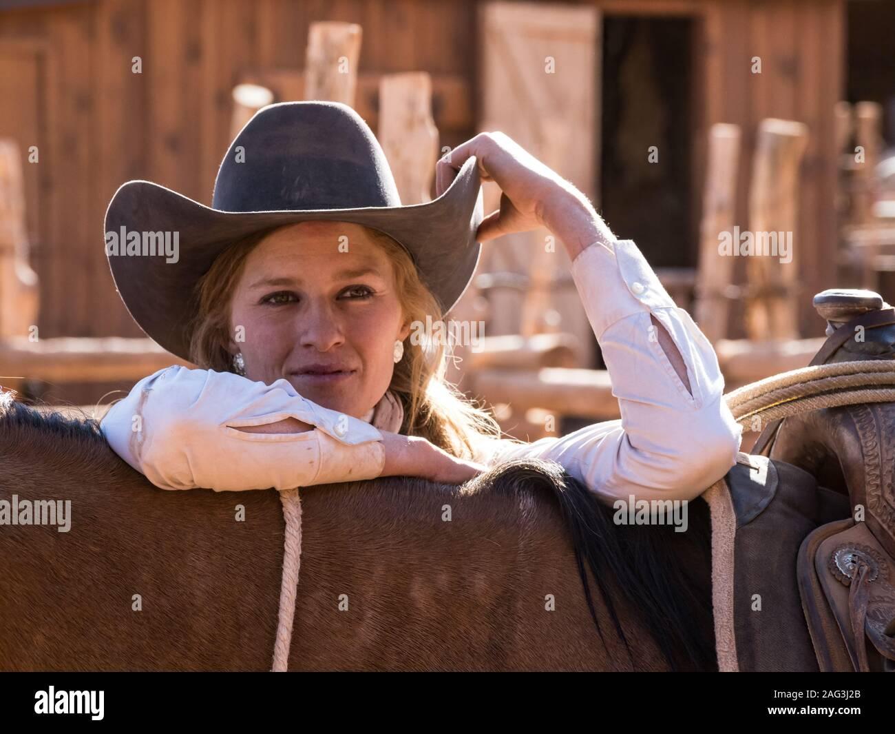 Un jeune groupe de travail attrayant wrangler cowgirl pose avec son cheval dans un ranch près de Moab, Utah. Banque D'Images