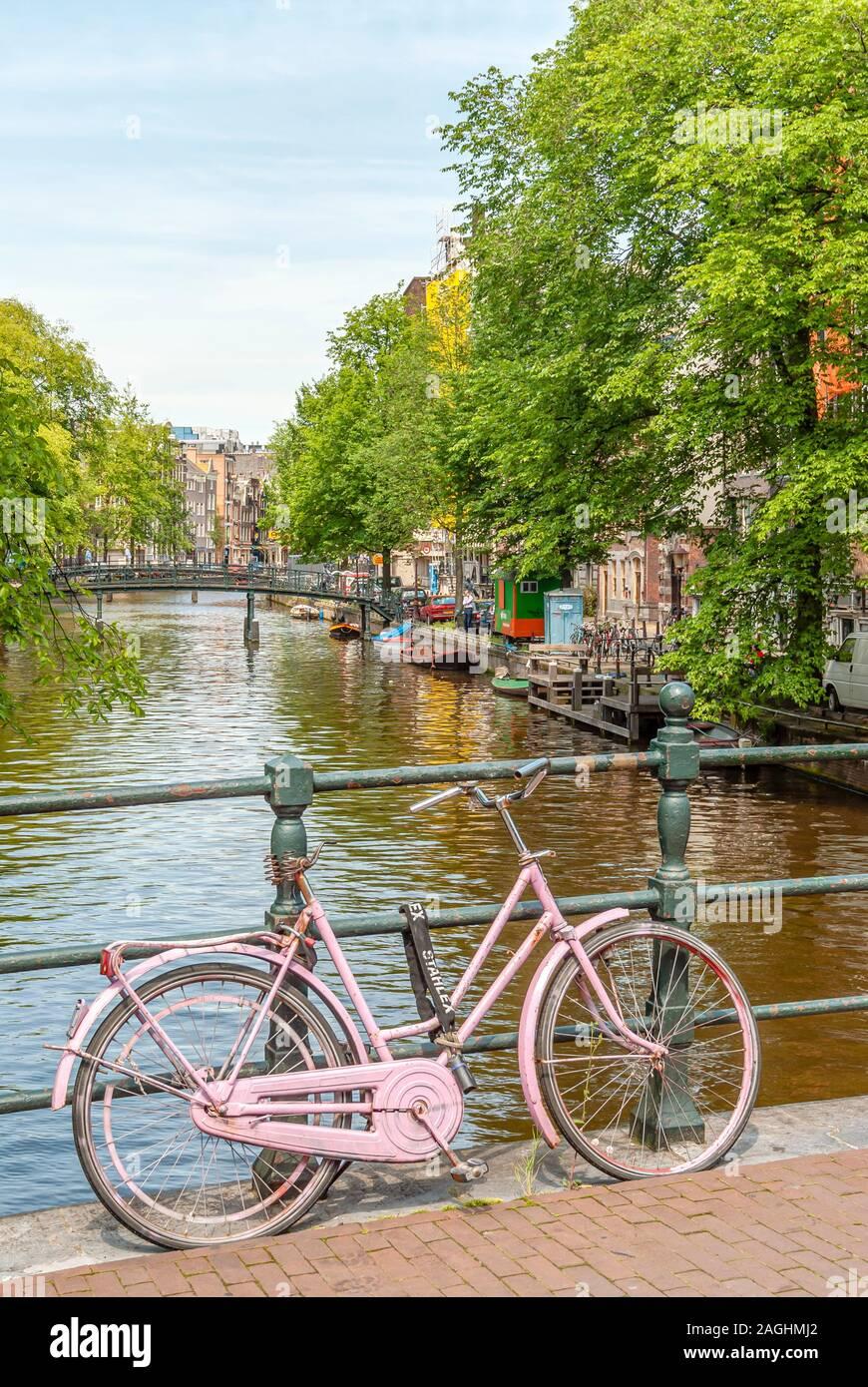 Vieux Vélo rose sur un pont dans le centre-ville d'Amsterdam, Netherlande Banque D'Images
