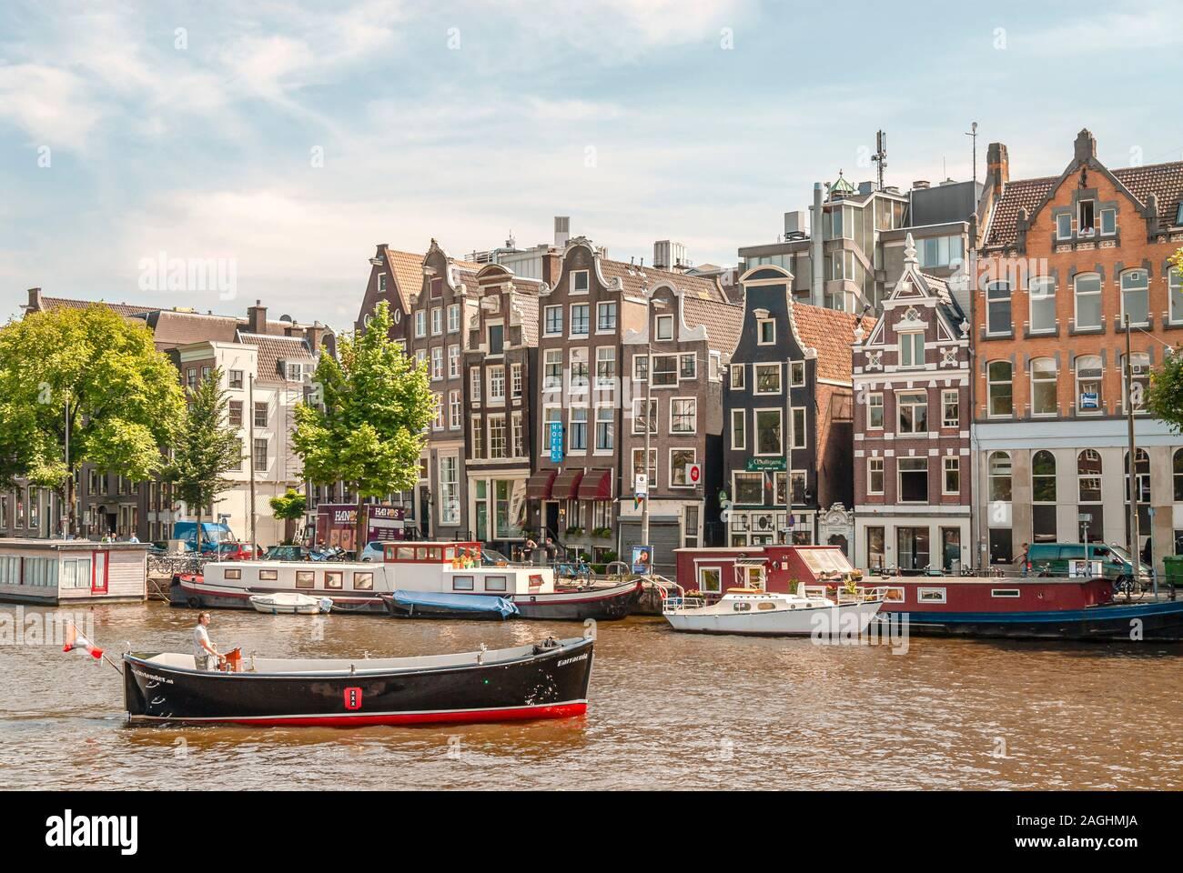 Architecture historique et bateaux à moteur au canal dans le centre-ville d'Amsterdam, Pays-Bas Banque D'Images