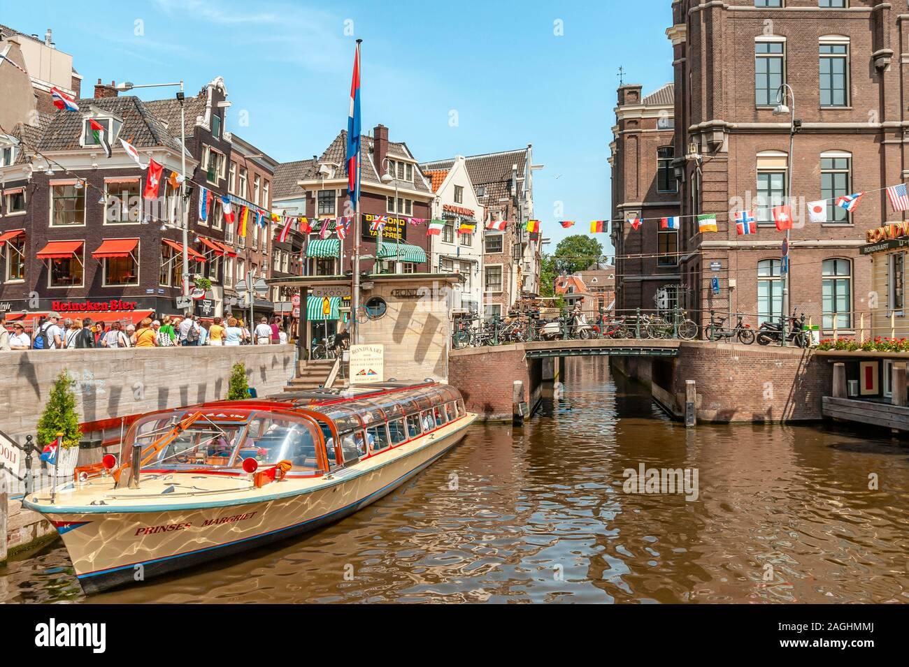 Des bateaux touristiques dans un canal d'eau dans le centre-ville d'Amsterdam, Pays-Bas. Banque D'Images