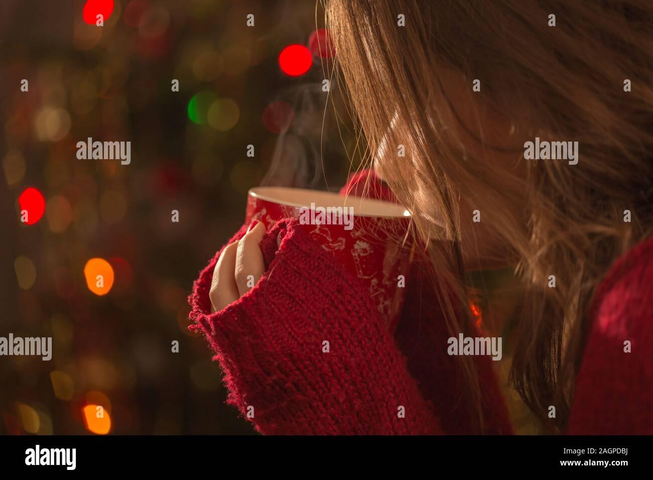 Jeune femme avec une tasse de chocolat chaud ou de thé ou de café en face de l'arbre de Noël. Noël et de détente concept. Banque D'Images