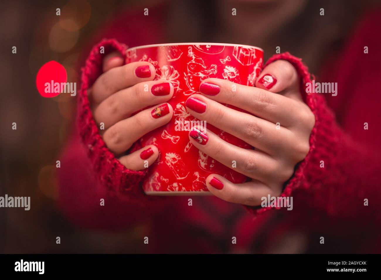 Woman's hand holding red une tasse de café. Avec une belle manucure d'hiver. Banque D'Images