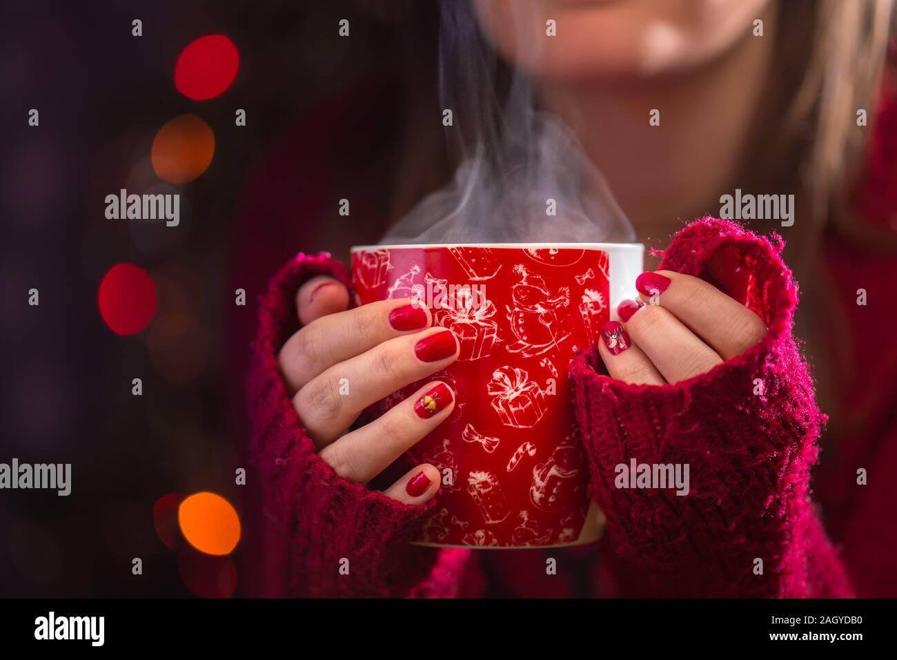 Détail de femme mains tenant une tasse de thé chaud à la vapeur. Noël arrière-plan flou. Concept d'hiver ou de noël. Banque D'Images