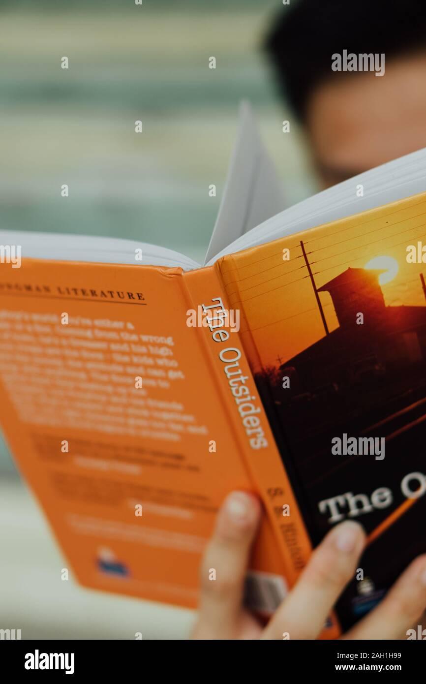La lecture d'un mâle de Singapour version couverture rigide de l'extérieur Banque D'Images