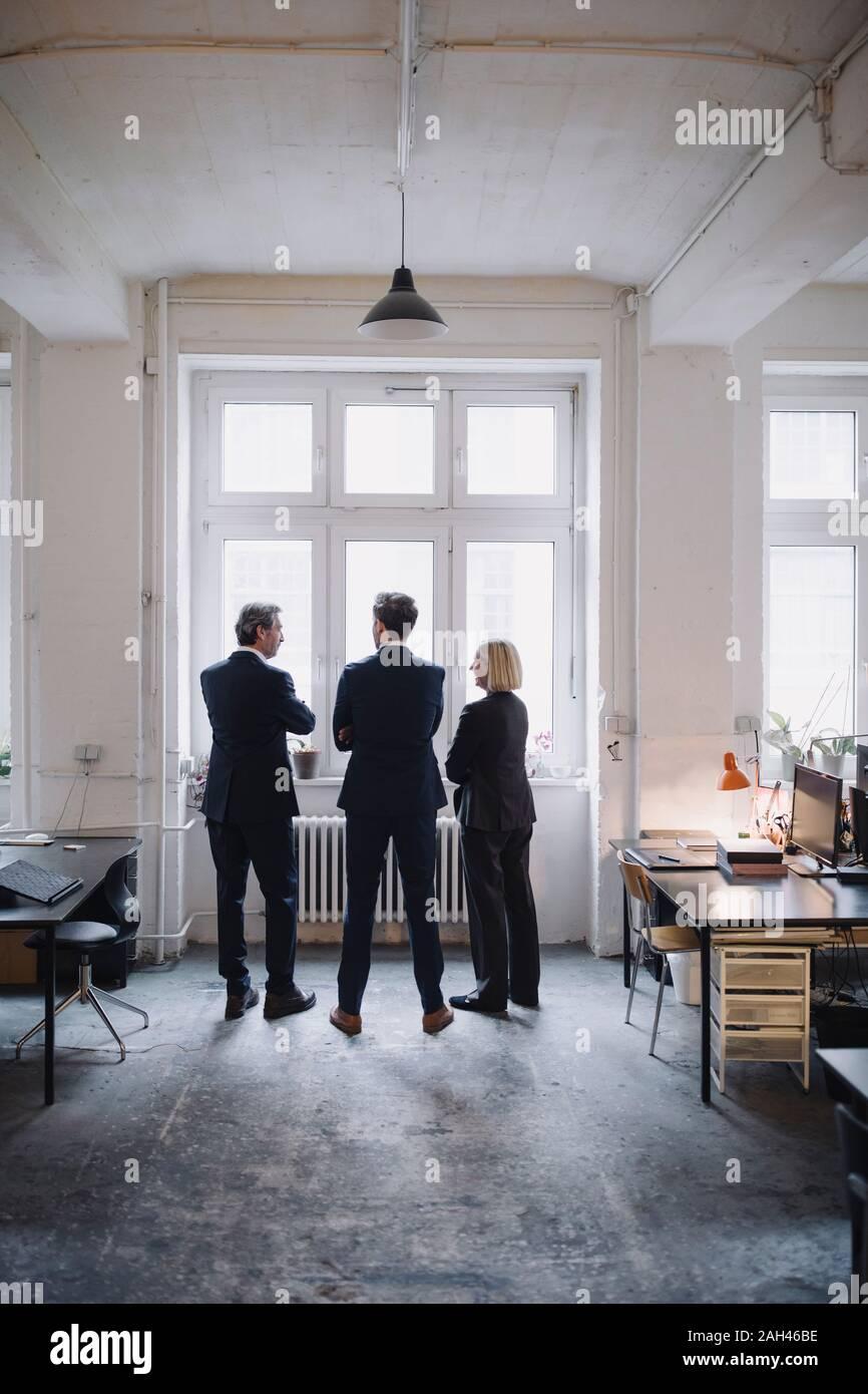 Les gens d'affaires debout à la fenêtre in office Banque D'Images