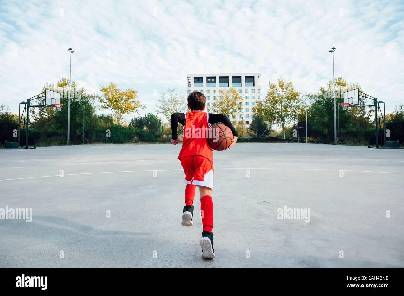 Garçon jouant au basket-ball à l'extérieur sur cour Banque D'Images