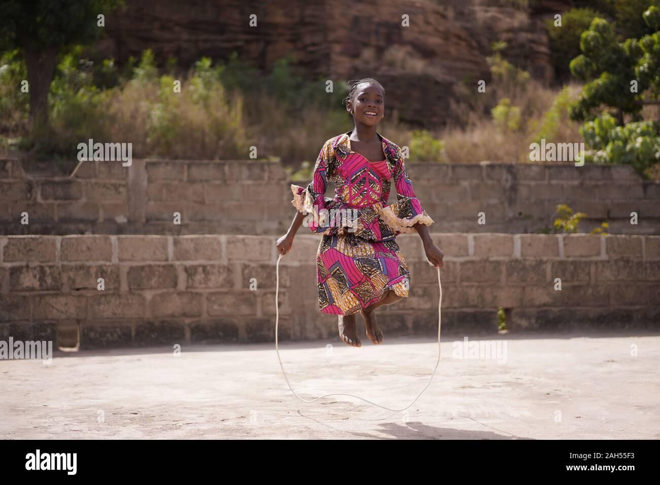 Souriante Jeune fille africaine se réchauffer avec une corde à sauter dans l'arrière-cour Banque D'Images