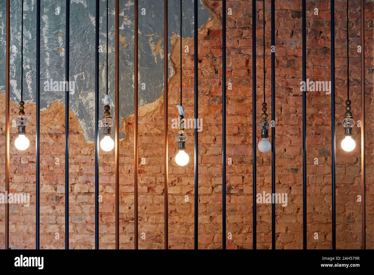 Ampoules de feu, suspendue dans une rangée, derrière des barreaux de fer, dans le contexte d'un mur de briques Banque D'Images