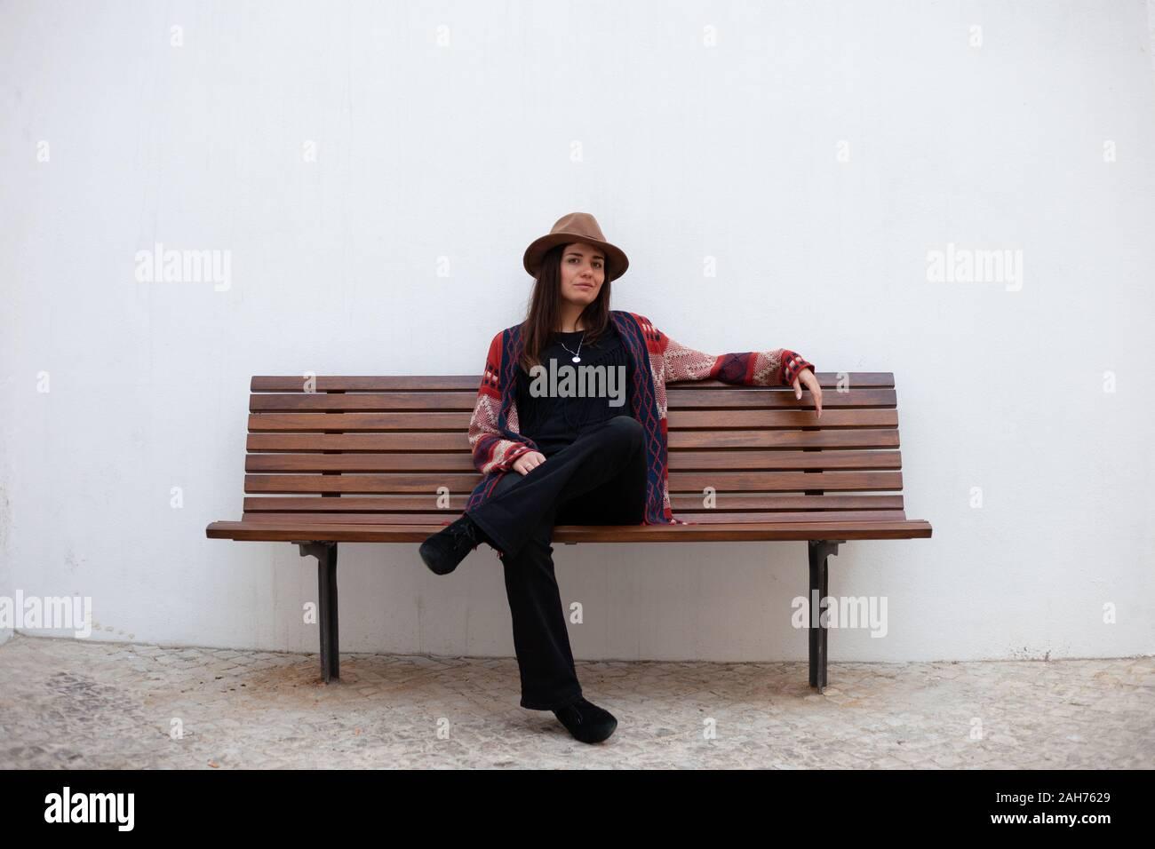 Belle femme élégante avec chapeau assis sur un banc de parc sur mur Banque D'Images