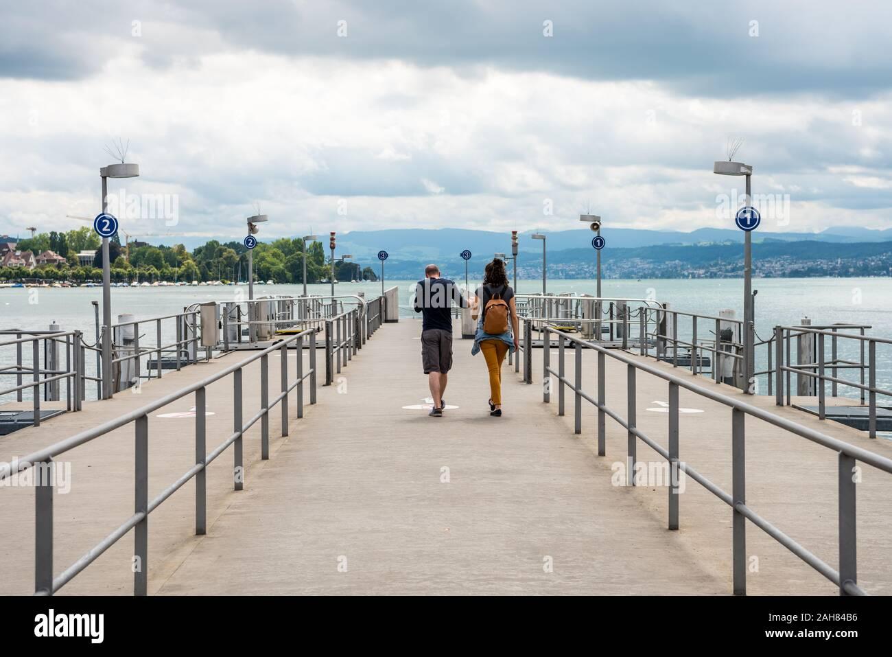 Couple aimant marcher à quai des navires de croisière sur le lac de Zurich avec fond de bâtiments au Lakeshore à Zurich, Suisse. Banque D'Images
