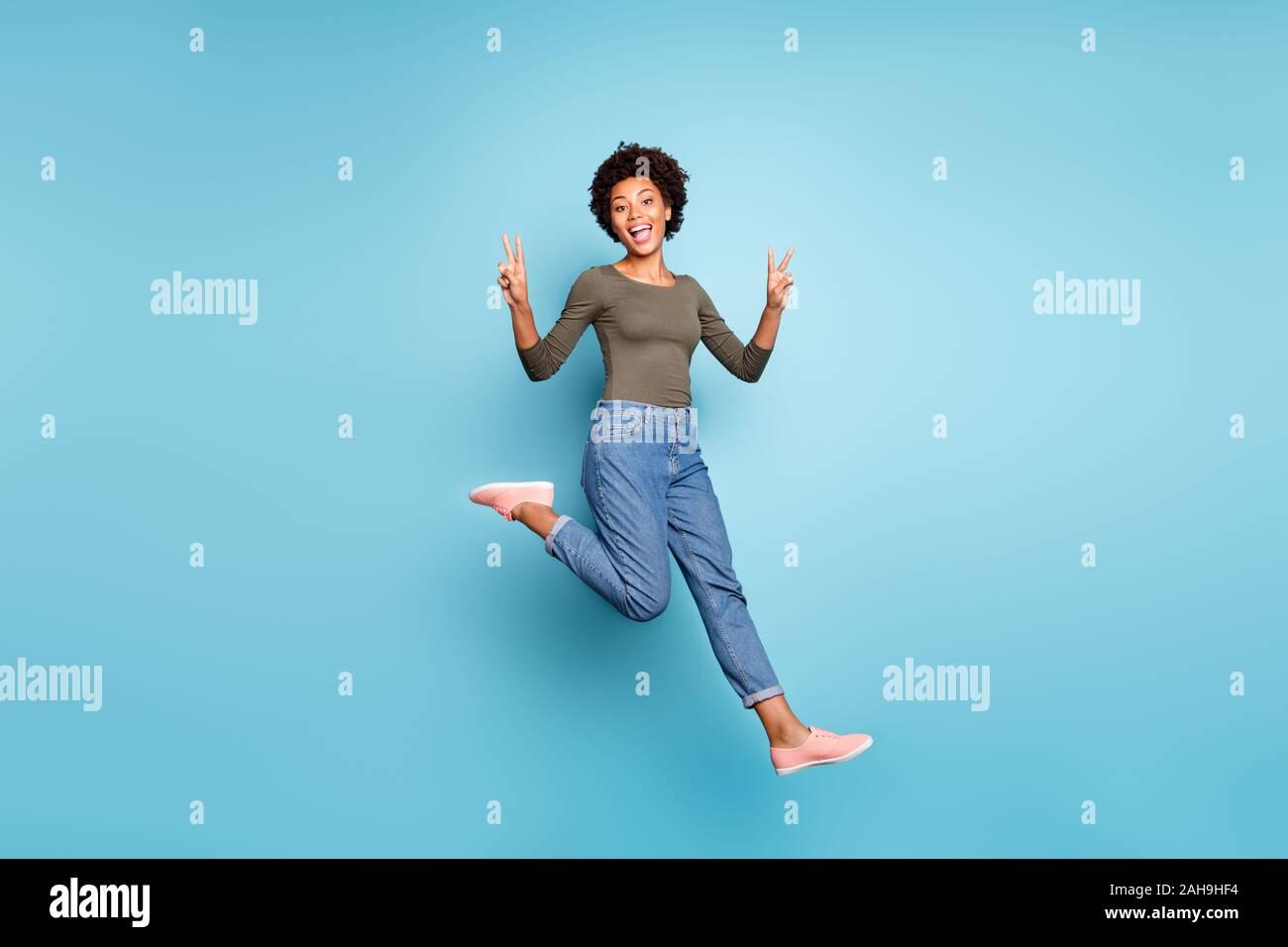 Toute la longueur de la taille du corps photo de joyeux cris drôles friendly nice woman jumping teint foncé denim jeans pull vert montrant vous v-sign isolated Banque D'Images