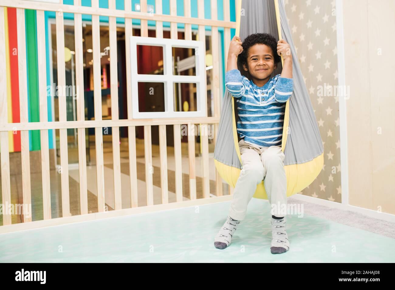 Happy little African boy dans casualwear assis dans un hamac suspendu au plafond Banque D'Images