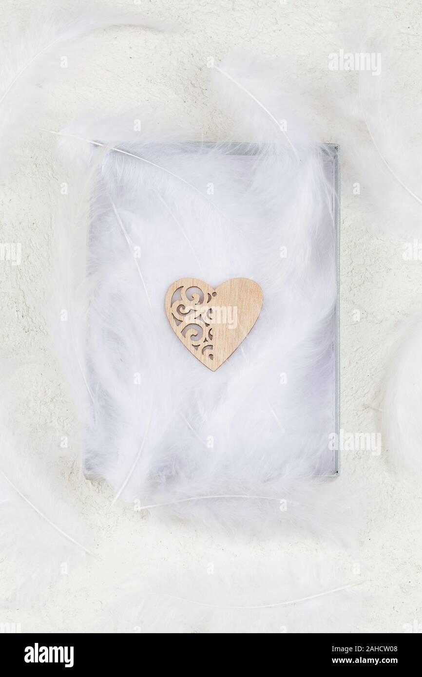Au coeur du bois des plumes blanches dans la boîte. Valentines Day background minimaliste. amour. symbole de l'élément de conception graphique pour les cartes de vœux, bannières, vente Banque D'Images